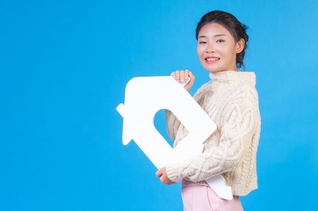 Eine schöne frau, die ein neues langärmliges weißes hemd mit einem haussymbol trägt. haushandel.