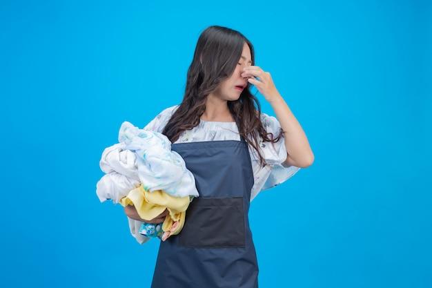 Eine schöne frau, die ein tuch anhält, bereitete vor sich, auf blau sich zu waschen
