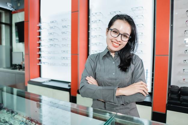 Eine schöne frau, die eine tragende brille gegen den hintergrund einer brillenvitrine in einer augenklinik aufwirft