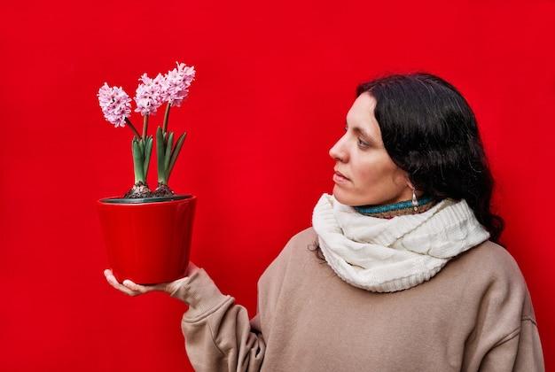 Eine schöne frau, die einen topf mit hyazinthenpflanzen auf roter wand hält