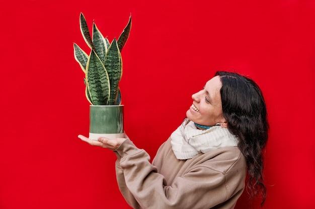 Eine schöne frau, die einen topf mit schlangenpflanzen an der roten wand hält