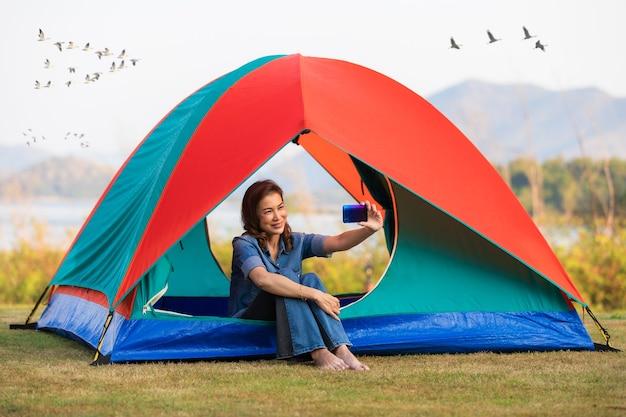 Eine schöne frau, die in einem campingzelt sitzt und smartphone verwendet, das selfie für sich mit großem see im hintergrund und gruppe von vögeln nimmt, die am morgen fliegen.