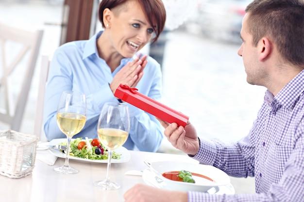 Eine schöne frau, die in einem restaurant von ihrem mann ein geschenk bekommt present