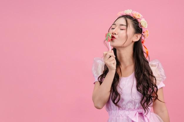 Eine schöne frau, die in einer rosa prinzessin gekleidet wird, spielt mit ihrer süßen süßigkeit auf einem rosa.