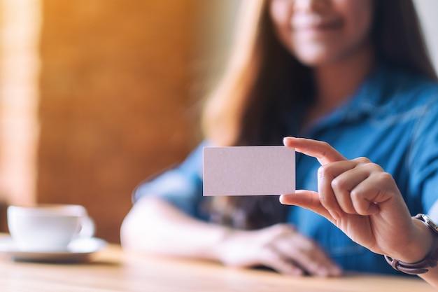 Eine schöne frau, die jemandem eine leere leere visitenkarte hält und zeigt