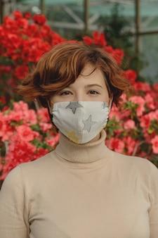 Eine schöne frau, die schützende gesichtsmaske unter frühlingsblumen trägt. coronavirus-pandemiekonzept