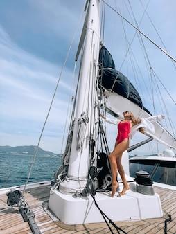 Eine schöne frau im bikini steht glücklich auf einer yacht und schaut auf das meer