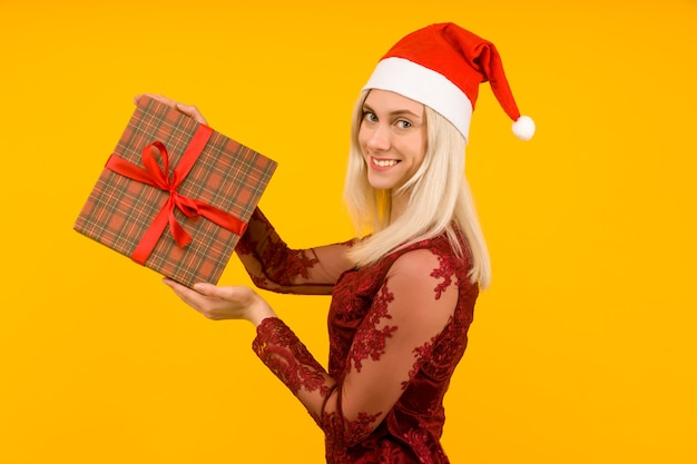 Eine schöne frau im weihnachtsmannhut und im roten kleid halten in den händen geschenke auf gelbem hintergrund feier von weihnachten