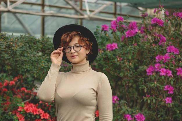 Eine schöne frau in brille und hut lächelnd zwischen den grünen pflanzen und blumen.