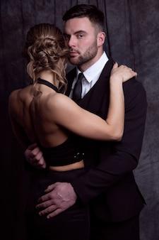 Eine schöne frau in einem abendkleid umarmt einen eleganten mann, der versucht, sie zu küssen