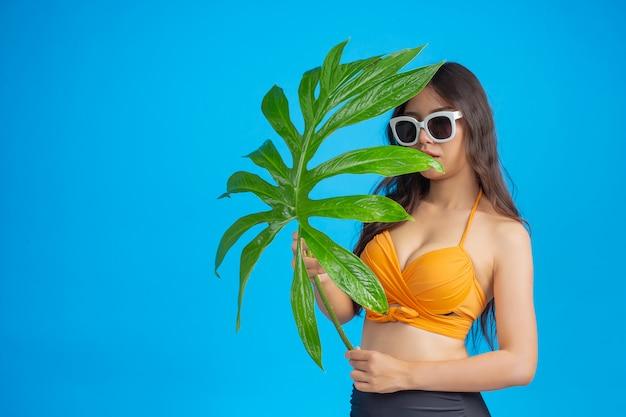 Eine schöne frau in einem badeanzug, der ein grünes blatt hält, wirft auf blau auf