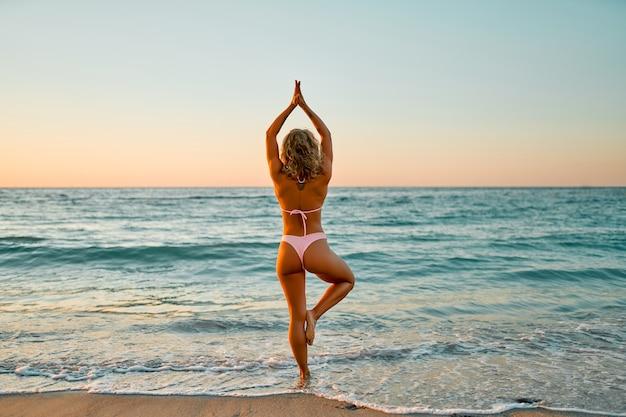 Eine schöne frau in einem bikini-badeanzug macht yoga am strand und genießt den klang der wellen und den schönen sonnenaufgang.