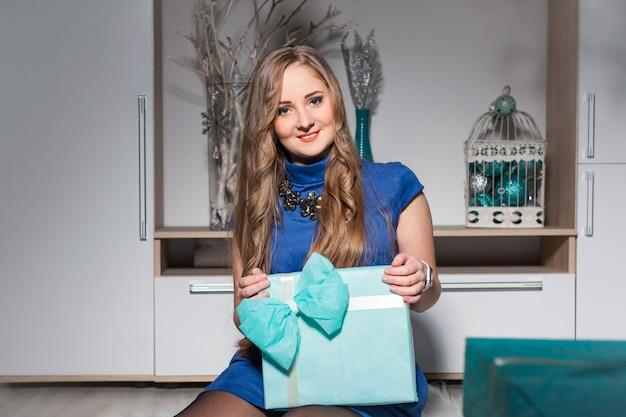 Eine schöne frau in einem blauen kleid mit langen haaren und einem geschenk sitzt auf dem boden und lächelt
