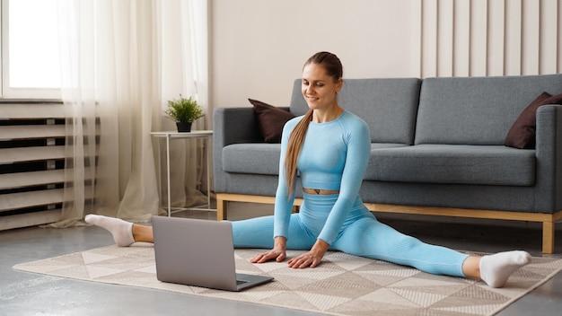 Eine schöne frau in einem blauen trainingsanzug streckt sich zu hause vor einem laptop. sie sitzt in einer querschnur und schaut sich online übungen an