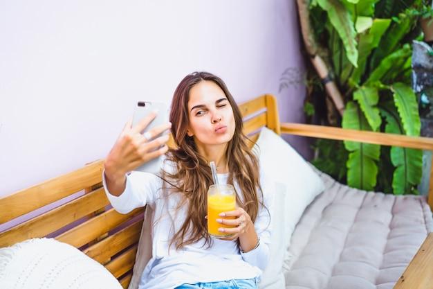 Eine schöne frau in einem café macht selfie auf einem smartphone, trinkt frisch gepressten saft.