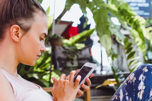 Eine schöne frau in einem café nutzt einen smartphone