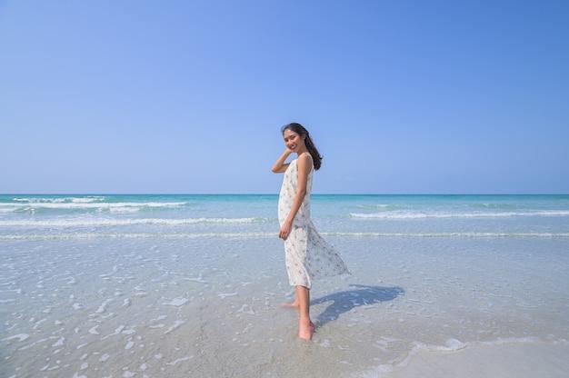 Eine schöne frau in einem entspannten weißen kleid und genießt den strand tagsüber.