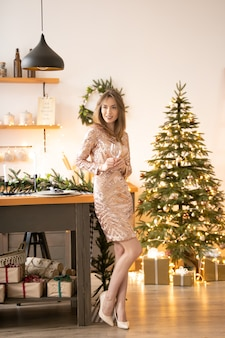 Eine schöne frau in einem festlichen kleid mit einem glas in der hand steht in der nähe des tisches vor dem hintergrund eines weihnachtsbaumes und einer girlande. neujahrsfeier, party. weicher fokus. vertikaler inhalt.