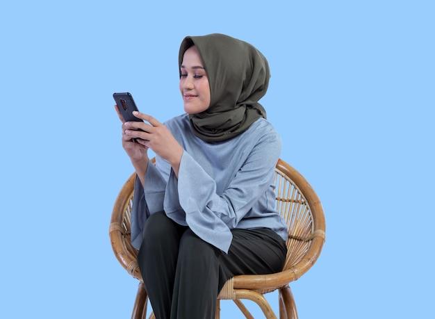 Eine schöne frau in einem hijab sitzt auf einem stuhl und schaut auf den telefonbildschirm