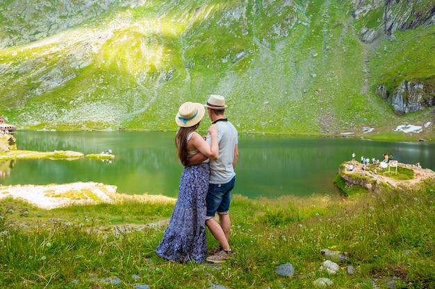 Eine schöne frau in einem langen kleid und strohhut umarmt mit mann in der nähe von see balea in rumänischen bergen.
