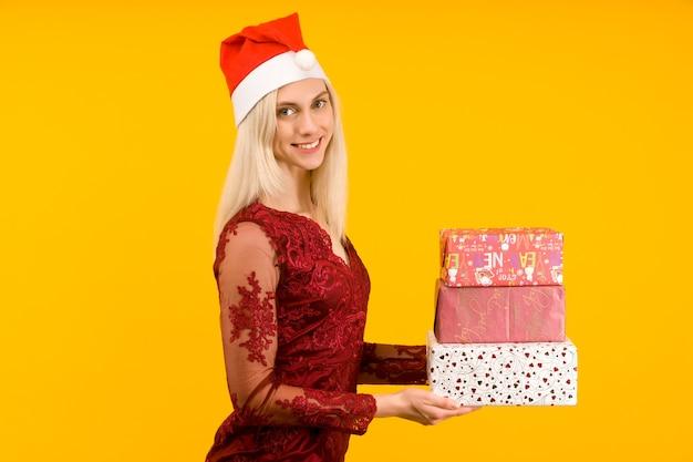 Eine schöne frau in einem neujahrshut halten in den händen geschenke auf gelbem hintergrund feier von weihnachten oder neujahr