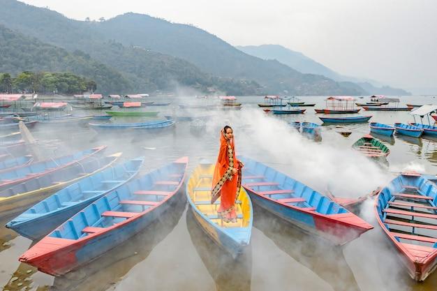 Eine schöne frau in einem sarianzug steht auf einem boot in pokhara nepal.