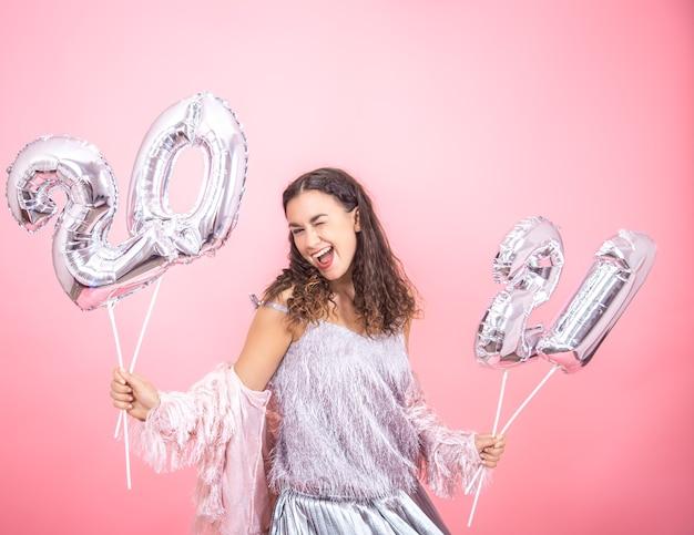 Eine schöne frau in einer festlichen stimmung, die mit silbernen luftballons für das neujahrskonzept tanzt