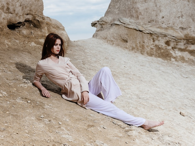 Eine schöne frau in leichter kleidung liegt im sand in den felsen für die natur