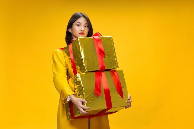 Eine schöne frau mit einem asiatischen aussehen hält geschenkboxen in ihren händen
