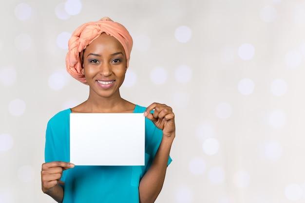 Eine schöne frau mit einem perfekten lächeln hält eine visitenkarte