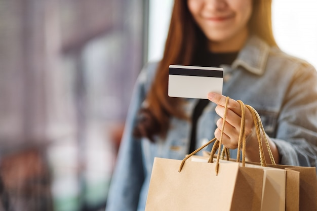 Eine schöne frau mit einkaufstüten, die eine kreditkarte für den kauf halten und verwenden