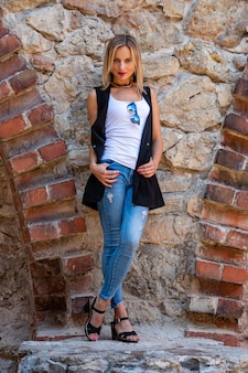 Eine schöne frau mit langen blonden haaren, einer weißen bluse und blauen jeans an der steinmauer der altstadt