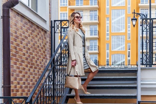 Eine schöne frau mit langen blonden haaren posiert an einem sonnigen tag in der nähe moderner gebäude. ein outdoor-porträt einer frau, die sich an das geländer lehnt.