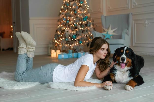 Eine schöne frau mit langen haaren liegt auf einem teppich vor dem hintergrund eines weihnachtsbaumes und neben ihr liegt ihr großer hund.