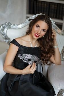 Eine schöne frau mit make-up in einem schwarzen kleid mit einer maske in der hand sitzt auf einem stuhl