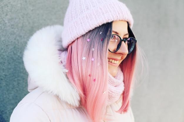 Eine schöne frau mit rosa haaren geht durch die straßen der stadt
