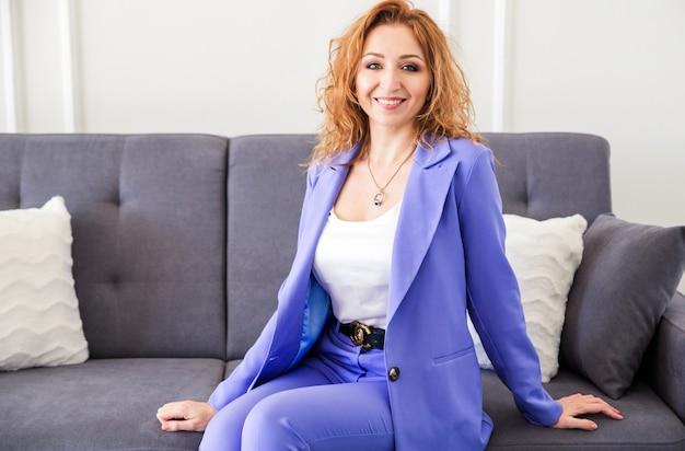 Eine schöne frau mit roten haaren in einem lila anzug sitzt auf einem grauen sofa und lächelt.