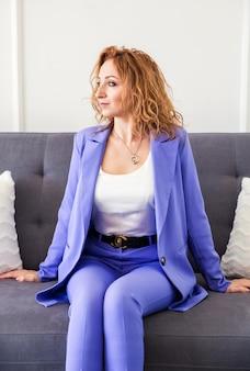 Eine schöne frau mit roten haaren in einem lila anzug sitzt auf einem grauen sofa und schaut weg.