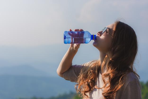 Eine schöne frau oben auf dem hügel und trinkwasser