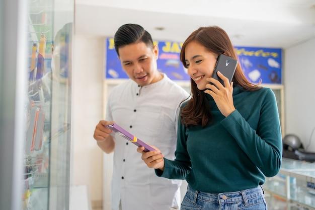 Eine schöne frau ruft mit einem mobiltelefon an, während sie mit einem gutaussehenden mann handyzubehör auswählt