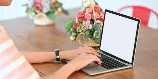 Eine schöne frau tippt auf einem weißen computer-laptop mit leerem bildschirm am hölzernen schreibtisch.
