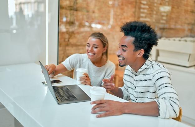 Eine schöne frau und ein afrikanischer mann trinken kaffee in einem café, arbeiten an einem laptop, plaudern und haben spaß.