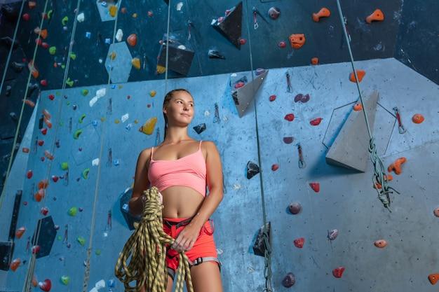 Eine schöne frau von europäischem aussehen in einem rosa trainingsanzug hält kletterseile