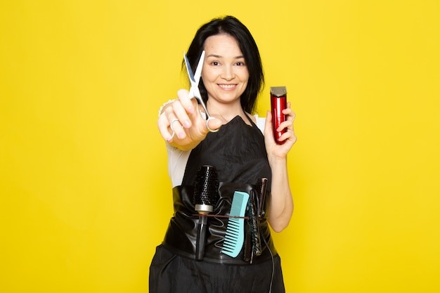 Eine schöne friseurin der vorderansicht im schwarzen umhang des weißen t-shirts mit bürsten mit gewaschenem haar, das schere und maschine hält, die auf dem friseurhaar des gelben hintergrundstylisten lächeln