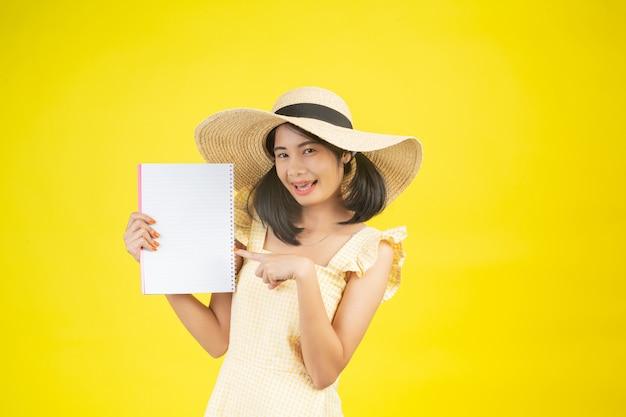 Eine schöne, glückliche frau, die einen großen hut trägt und ein weißbuch auf einem gelb hält.