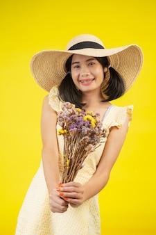 Eine schöne, glückliche frau, die einen großen hut trägt und einen blumenstrauß von trockenblumen auf einem gelb hält.