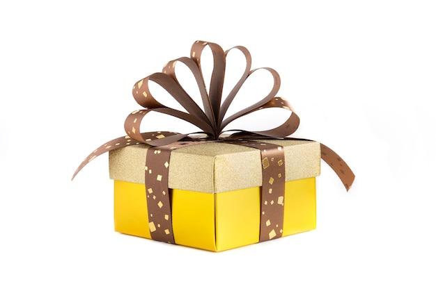 Eine schöne goldfarbene geschenkbox aus papier mit braunem und goldenem band