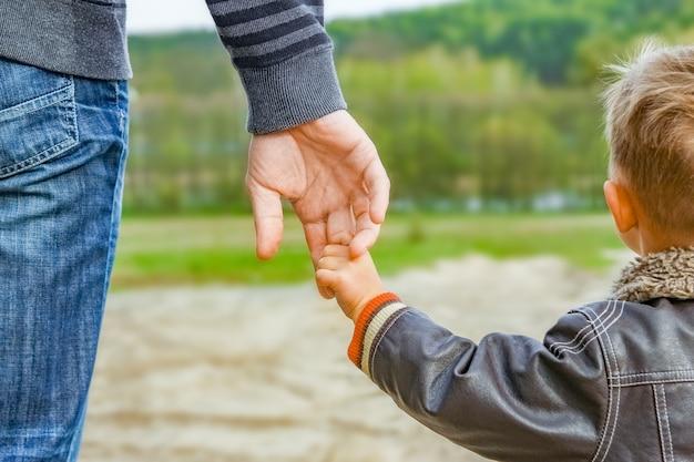 Eine schöne hand von eltern und kind im freien im park