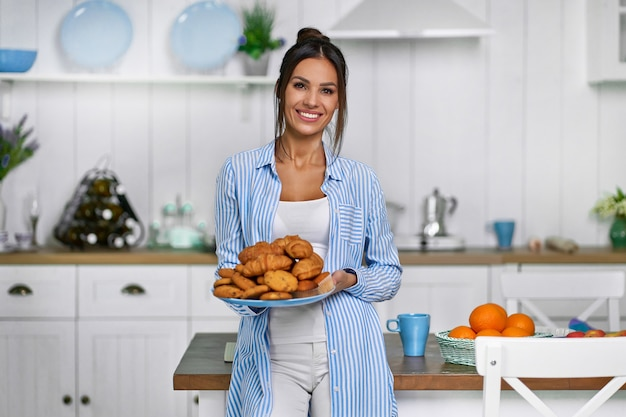 Eine schöne hausfrau steht in der küche und hält einen teller mit croissants und keksen