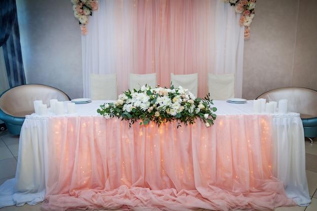 Eine schöne hochzeitsdekoration mit einem rosenstrauß in einer glasvase auf dem tisch.